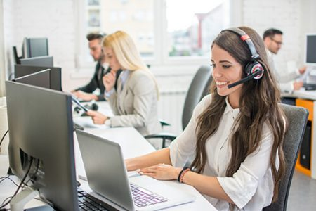 contact center staff with headset at computer and laptop